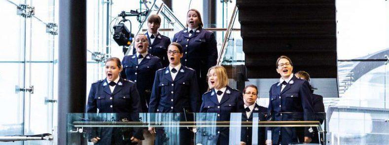 Kuorolaisia laulaa Musiikkitalossa portaikossa.