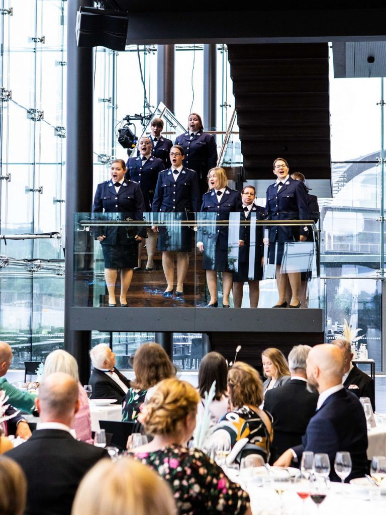 Kuorolaisia laulaa Musiikkitalossa portaikossa