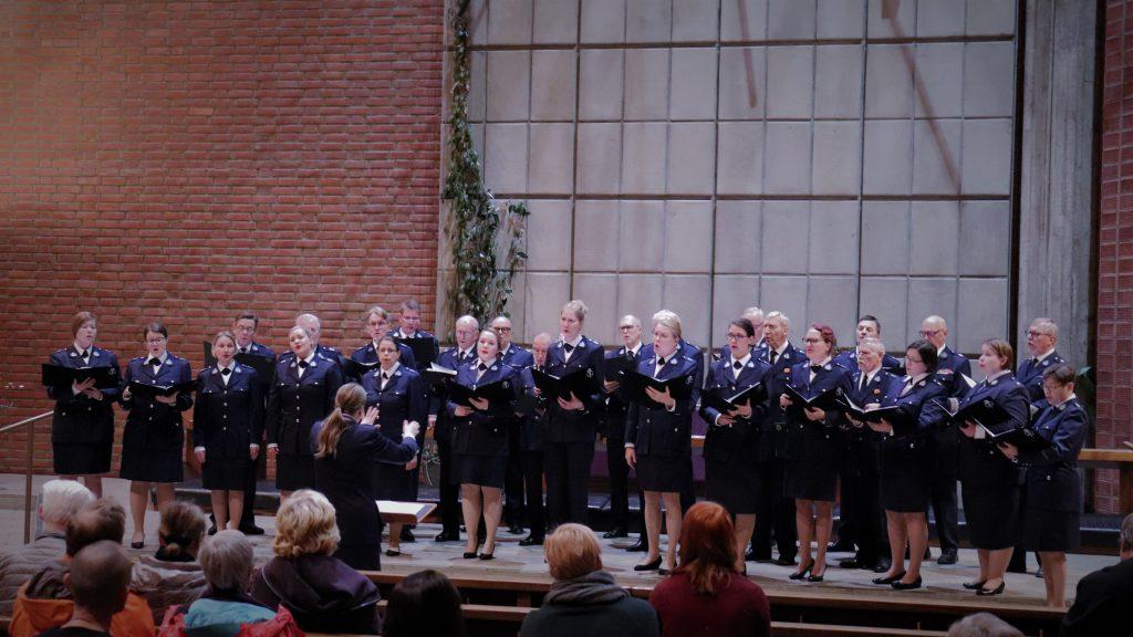 kuoro Roihuvuoren kirkon alttarilla laulamassa yhdessä Helsingin Poliisilaulajien kanssa